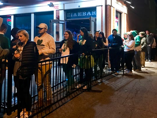 People wait in line to get into The Woods downtown