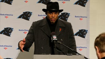 Carolina Panthers quarterback Cam Newton wears a black coat and hat as he talks with reporters during a post-game news conference after an NFL football game, Sunday, Dec. 4, 2016, in Seattle.