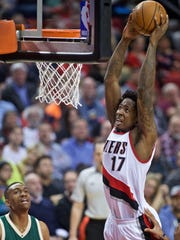 Portland Trail Blazers center Ed Davis dunks as Milwaukee Bucks forward Jabari Parker watches during the second half of an NBA basketball game in Portland, Ore., Tuesday, Feb. 2, 2016.