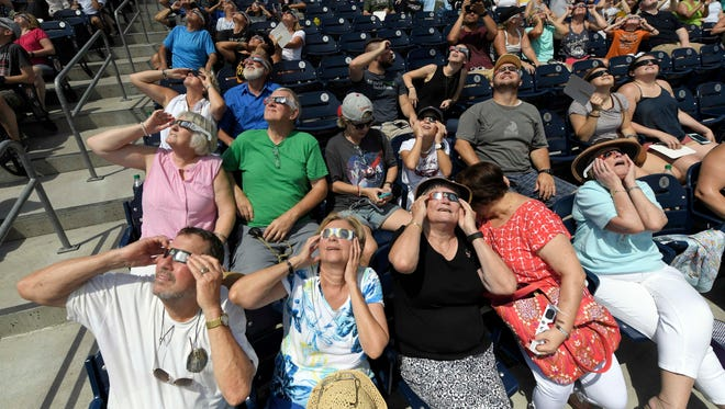 The crowd at the Nashville eclipse-viewing party watches the start of the eclipse at First Tennessee Park.