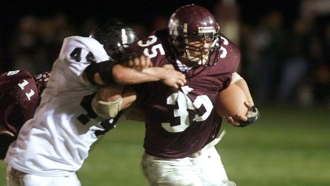 Cal-Mum running back Adam Cappotelli (35) trying to get away from LeRoy's Matt VanAlst. during a game in 1999.
