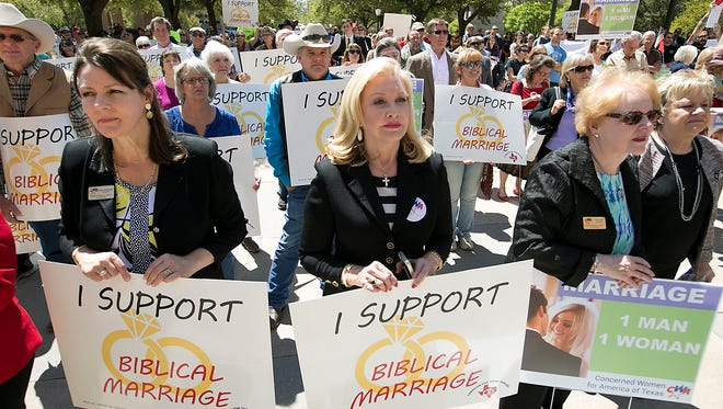 From left to right, Cindy Asmussen, Jan Jones and Mary Smith hold signs at a rally as they oppose gay marriage during a Defense of the Texas Marriage Amendment Rally outside of the state Capitol on March 23, 2015 in Austin.