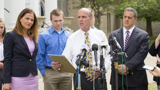 Cal Harris reads his statement  after his third murder trial ended with a hung jury and mistrial. From left, defense attorney Aida Leisenring, his son Taylor, Harris and his attorney Bruce Barket.