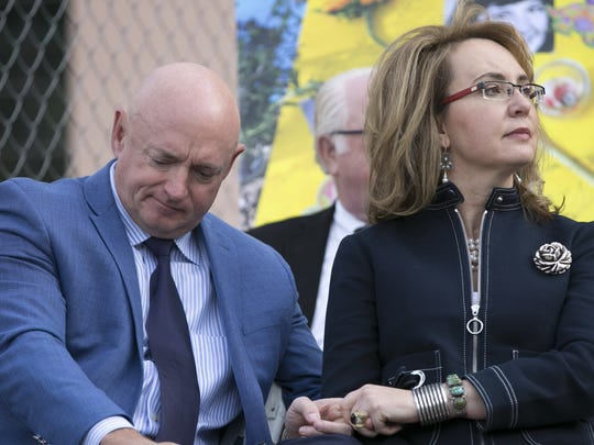 Former  U.S. Rep. Gabrielle Giffords holds the hand