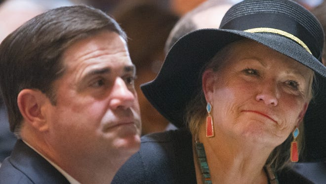 Gov. Doug Ducey and Beth Castro, daughter of former Gov. Raul Castro, listen to a mariachi performance during a memorial for the late governor at the state Capitol on May 16, 2015.