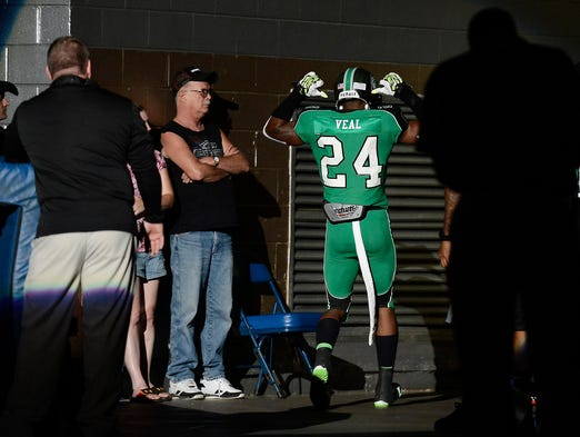 Venom defensive back Kenny Veal (24) points to his name on his jersey as he is introduced before the start of the Professional Indoor Football League championship game Saturday at Municipal Auditorium.