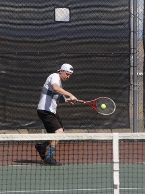 Farmington's Ned Merrion returns a serve during the Farmington Invitational on Saturday at the Farmington Tennis Complex.