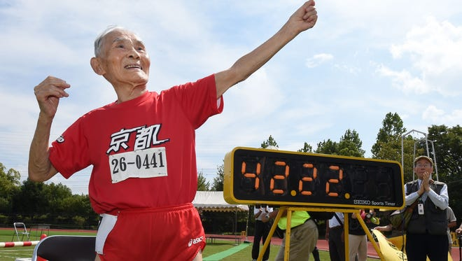 Hidekichi Miyazaki (in red), 105, imitates the pose of Usain Bolt after running with other competitors over eighty years of age during a 100-metre-dash in the Kyoto Masters Autumn Competiton in Kyoto, western Japan, on September 23.