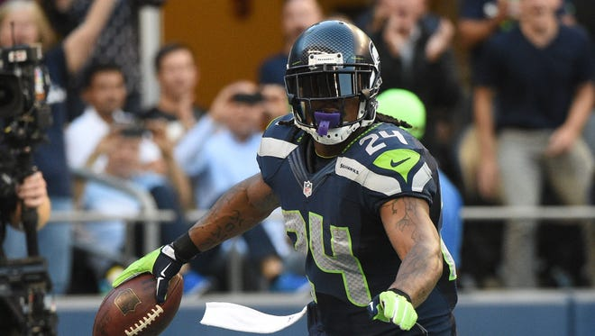 Seattle Seahawks running back Marshawn Lynch (24) celebrates after scoring a touchdown against the Green Bay Packers during the second quarter at CenturyLink Field.