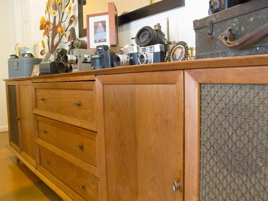 A vintage stereo cabinet in the dining room once belonged to Gottlieb's grandparents. Kuty and Gottlieb replaced the speakers and now use the piece as a multi-functional music and storage unit. The old cameras displayed on top came from various family members.
