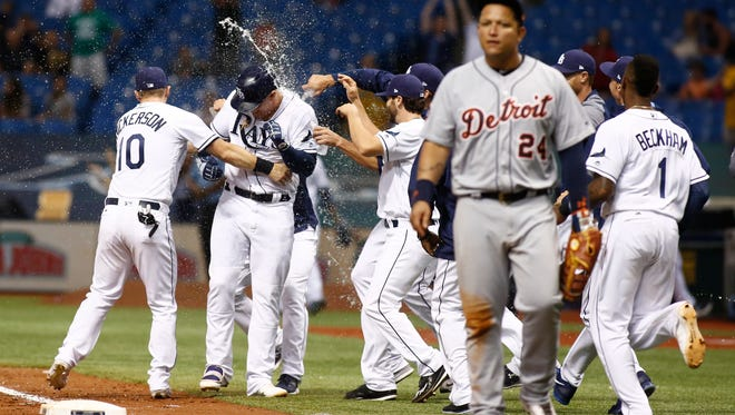 Rays players celebrate the win while Detroit's Miguel Cabrera looks on at the end of the game.