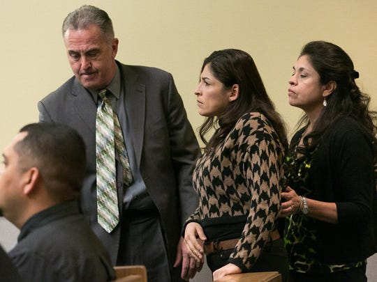 Embezzlement victim Maribel Samaniego, center, is escorted to speak before the court on Friday by Doña Ana County District Attorney Mark D'Antonio, left, and Lucy Jimenez, victim's advocate.