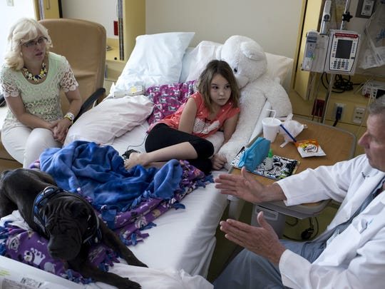 Emily Thomas, 10, and her mom, Debra Thomas (left), talk with Emily's doctor in her room at Cardon Children's Medical Center in Mesa on Friday, Aug. 14, 2015.