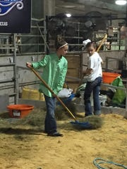 Madeline (left) and Carlisle clean the barn at their home in Refugio.
