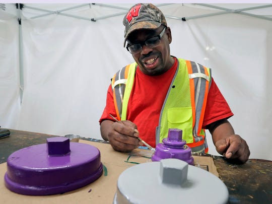 Chas Robinson, who paints caps for new hydrants at
