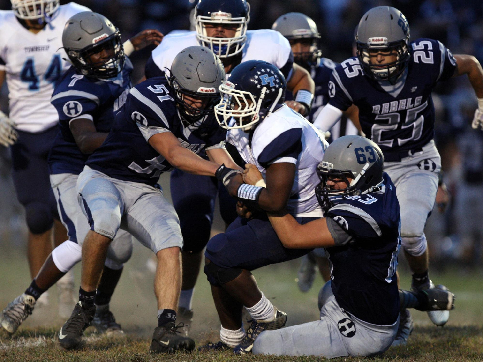 Rychard Hanshaw, #22 Freehold Township, is tackled by Conor Devine, #51 Howell, left, and Michael Ioannides, #63, right, and other defenders in a football game Friday, September 25, 2015, at Howell High School.