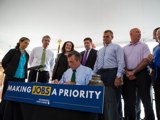 Gov. John Carney signs a bill amending the Coastal Zone Act during an event at the former site of General Chemical Corp. in Claymont.
