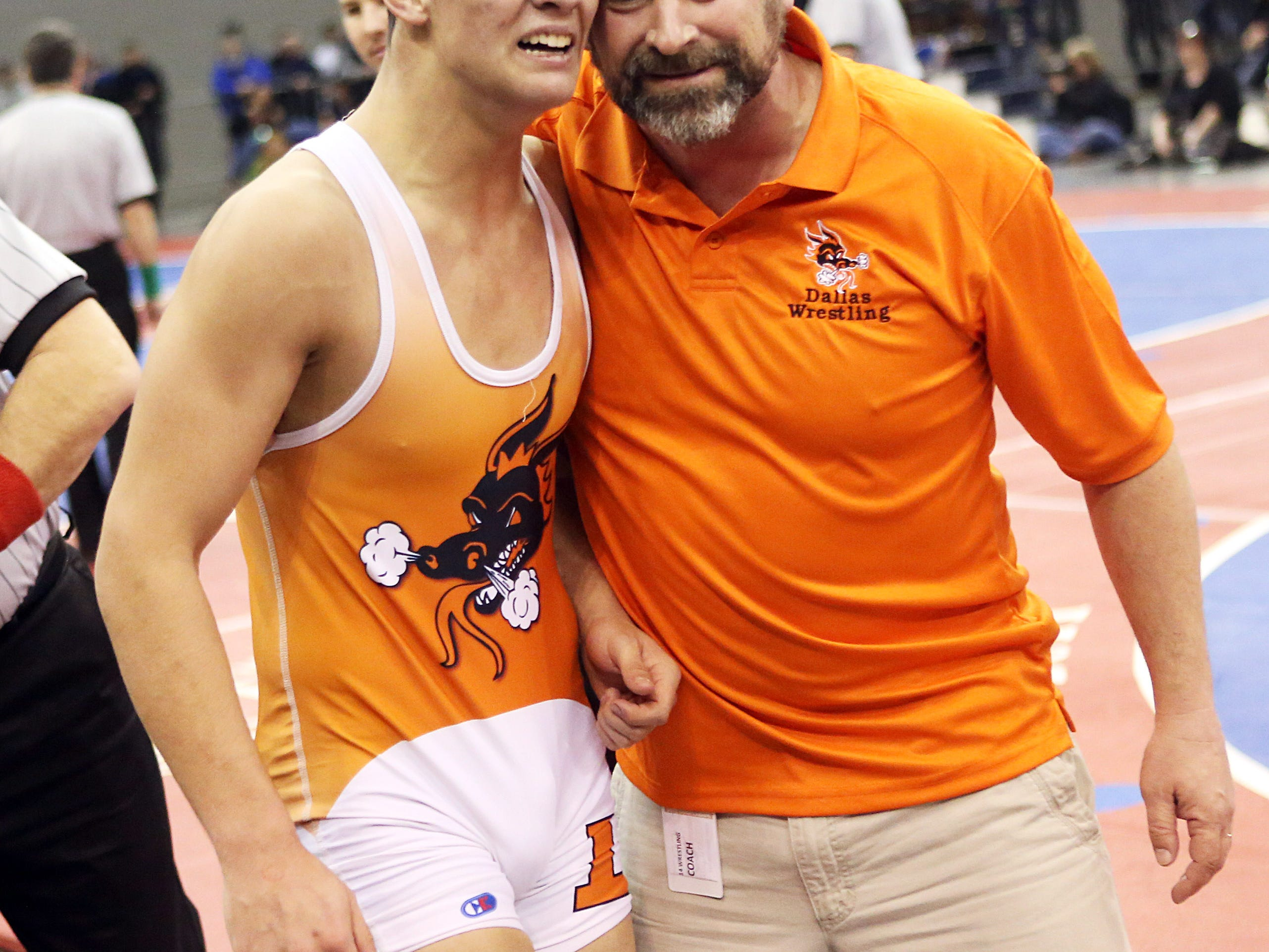 Dallas coach Tony Olliff (right) hugs Dallas' Ryan Spencer after his Spencer won the 2014 state championship.