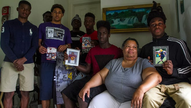 Stephanie White, Stef'An Strawder's mother, is surrounded by her son's friends and teammates Monday afternoon at her home in Lehigh Acres. Her son's friends and teammates were visiting to provide her with support as she grieved her son's loss earlier that day during a shooting in Fort Myers.