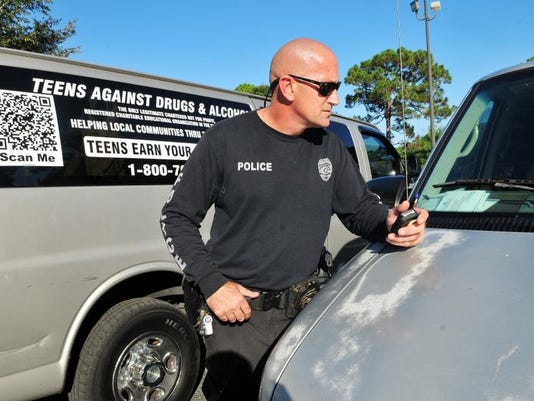 Officer Chris Jones of the Palm Bay Police Department looks over two vans with wood benches and partitions with breathing