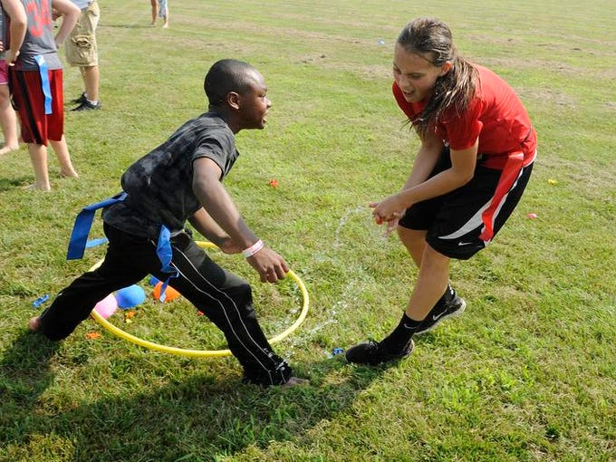 Amonie Akens defends the blue teams water balloon stash from red team player Jayme Hottinger during a water themed game at the Active Fit Field Day on Tuesday, July 22, 2014. The field day featured games including kick ball, touch football, soccer, and freeze tag and ended with games played under sprinklers for a cool down.