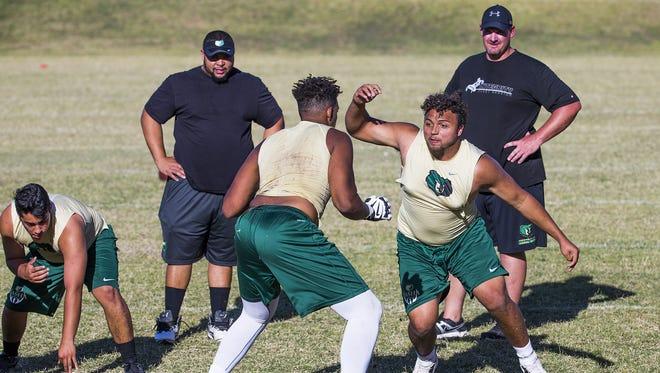 Basha High School Football lineman Jonathan Nathaniel, white leggings, prepares to block Brandon Myree, right, during spring football practice at the school, Monday, May 9, 2016.