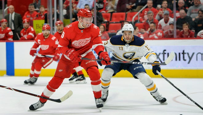 Red Wings right wing Anthony Mantha goes for the puck as he is chased by Sabres right wing Nicholas Baptiste during the second period Thursday, Feb. 22, 2018 in Detroit.