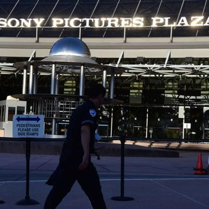 A security guards walks past the entrance to Sony Pictures