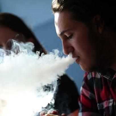 Kieran Thomas smokes an e-cigarette at Digita Ciggz
