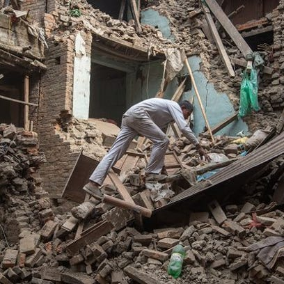 A man climbs on top of debris after buildings collapsed
