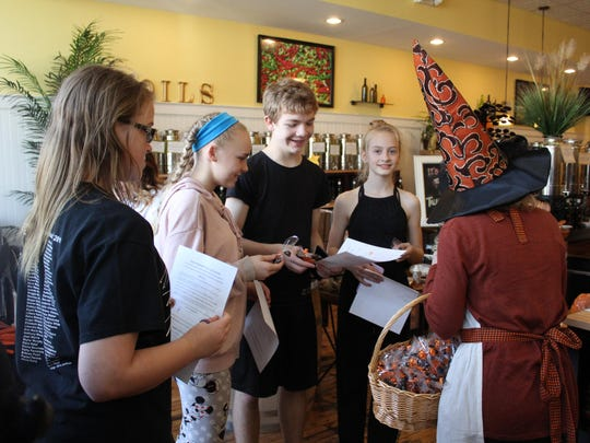 Alyssa Weber, 16, Kylee Macri, 12, Ethan Gale, 13, and Katrina Applegate, 11, get some treats from Kelly Brown, owner of Tales of the Olive, after the group stopped in during their scavenger hunt.
