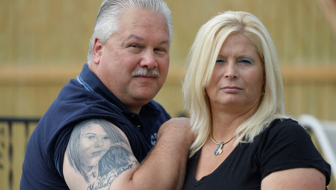 Tom and Lisa Moore pose outside their home in Terre Haute, Ind. on Oct. 3, 2013.