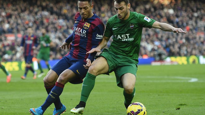 FC Barcelona's Adriano, from Brazil, left, duels for the ball Levante's Ivan Lopez during a Spanish La Liga soccer match at the Camp Nou stadium in Barcelona, Spain, Sunday, Feb. 15, 2015. (AP Photo/Manu Fernandez)