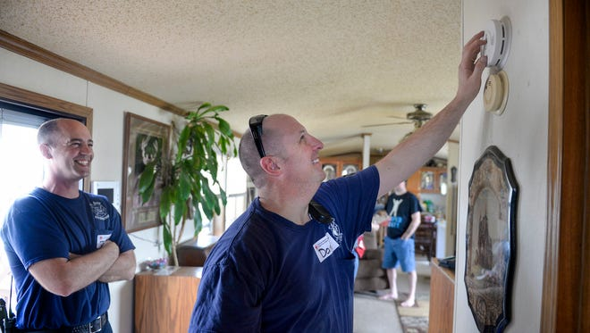 St. Cloud firefighters Jeff Gendreau, left, and Dan Ford install and test a smoke detector in a mobile home Saturday, April 23, in the Cloverleaf Mobile Home Community. American Red Cross volunteers and St. Cloud Fire Department planned to install an average of two to three detectors in 130 homes in the area.