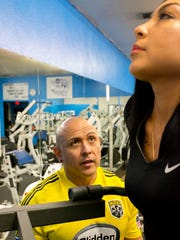 Stefanie Hernandez works out on an assisted dip machine at the Las Cruces Fitness Center while her personal trainer Johnny Jimenez looks on. Hernandez has been training with Jimenez three times a week for a year and says exercising regularly makes her feel great.