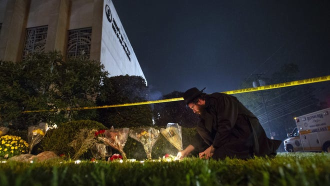In this Oct. 27, 2018, photo, Rabbi Eli Wilansky lights a candle after a mass shooting at Tree of Life Synagogue in Pittsburgh's Squirrel Hill neighborhood.