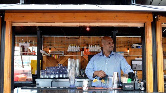 Mario Victoria Vasquez spots a patron that needs to be seated while making a couple drinks at the outdoor bar at Amore Victoria Ristorante, which is owned by his family in Minneapolis.