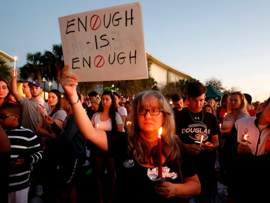 Mourners stand during a candlelight vigil for the victims