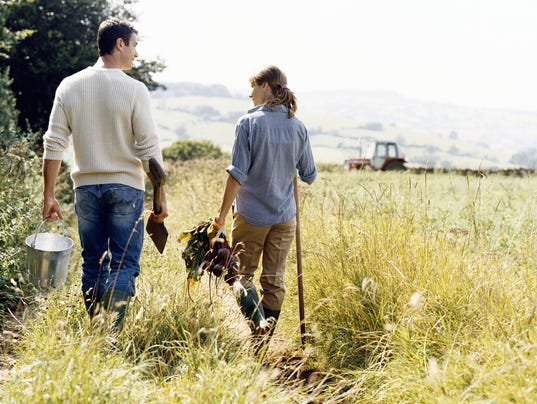 Farming Couple Walking in a Field Holding Bucket, Spade and Vegetables