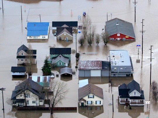 "This Jan. 8, 2009 file photo shows homes surrounded by floodwaters from the Chehalis River in Chehalis, Wash. In early 2009, heavy rains and melting snow caused flooding in parts of Washington, leading to a leak in the earthen abutment of the Howard Hanson Dam. Officials in King County and several cities placed giant sandbags atop downstream levees, erected flood guards around facilities such as a jail and sewage treatment plant, and temporarily relocated the county election office. ""FEMA staff told us, `We understand why you did what you did, and it was a reasonably prudent thing to protect the public,'Ó said Mark Isaacson, King CountyÕs wastewater treatment director who at the time led its flood control division. But it didn't fall within their definition of imminent flooding."""