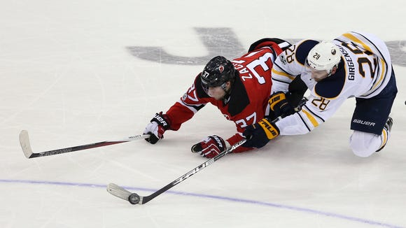 Buffalo Sabres center Zemgus Girgensons, of Latvia, (28), controls the puck as he collides with New Jersey Devils center Pavel Zacha, of Czech Republic, (37) during the third period of an NHL hockey game, Monday, Feb. 6, 2017, in Newark, N.J. The Devils won 2-1. (AP Photo/Mel Evans)