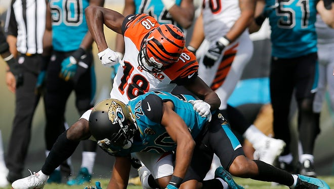 Cincinnati Bengals wide receiver A.J. Green (18) pulls back to throw a second punch to the helmet of Jacksonville Jaguars cornerback Jalen Ramsey (20) after a play late in the second quarter of the NFL Week 9 game between the Jacksonville Jaguars and the Cincinnati Bengals at EverBank Field in Jacksonville, Fla. At halftime the Bengals trailed 10-7 after wide receiver A.J. Green was ejected for throwing a punch.