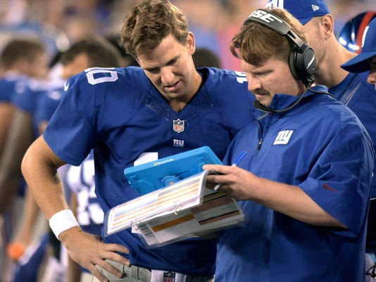FILE - In this Aug. 22, 2015, file photo, New York Giants offensive coordinator Ben McAdoo confers with quarterbacks Eli Manning, left, and Ryan Nassib, right, during the first half of a preseason NFL football game in East Rutherford, N.J. A person familiar with the decision tells The Associated Press the Giants are hiring offensive coordinator Ben McAdoo as their next head coach. McAdoo, 38, is being given the job a little more than a week after Tom Coughlin stepped down after 12 seasons, the person spoke Wednesday on condition of anonymity because the team has not officially announced the hiring. (AP Photo/Bill Kostroun, File)