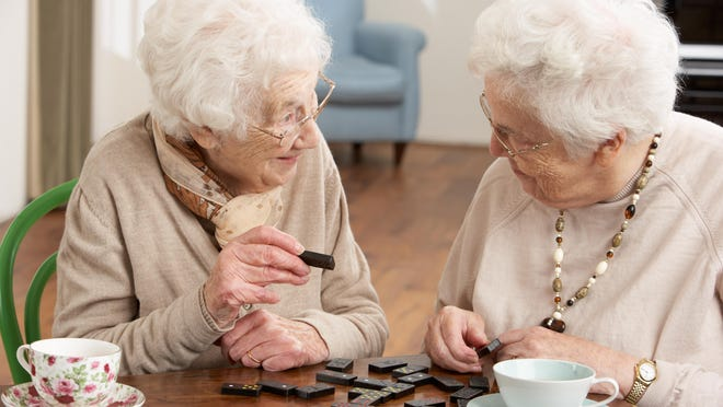 Two Senior Women Playing Dominoes At Day Care Centre With Cups Of Tea