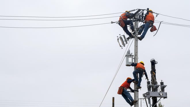 A team of linemen repairs power lines to restore power after a storm.