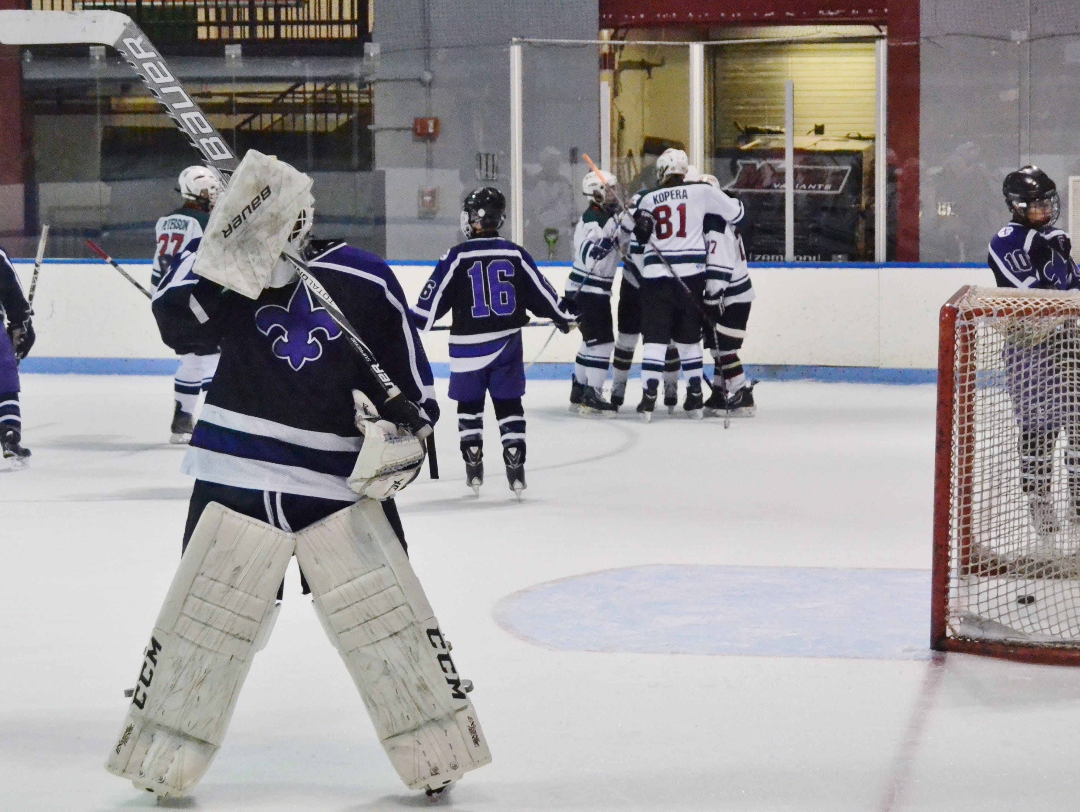New Rochelle goalie Arthur Liebowitz reacts while Rivertown forward Alex Inglis celebrates a first-period goal with his linemates. The Legends moved on with a 4-1 win and will face Mamaroneck on Wednesday.