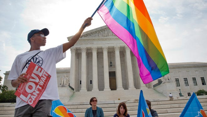 Carlos McKnight, 17, of Washington, holds up a flag in support of gay marriage outside of the Supreme Court in Washington, Friday June 26, 2015. A major opinion on gay marriage is among the remaining to be released before the term ends at the end of June. (AP Photo/Jacquelyn Martin)