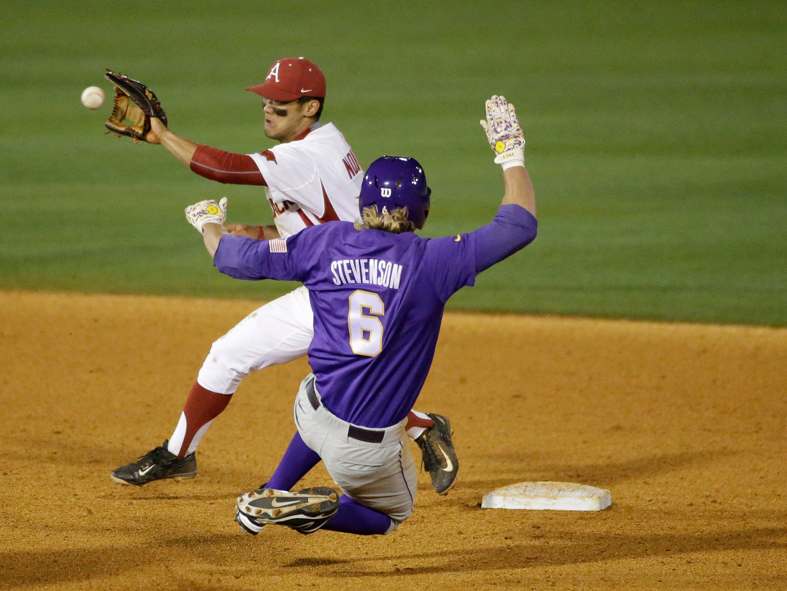 Arkansas' Rick Nomura, left, tags out LSU's Andrew Stevenson during the seventh inning of a Southeastern Conference tournament game at the Hoover Met on Thursday in Hoover, Ala.