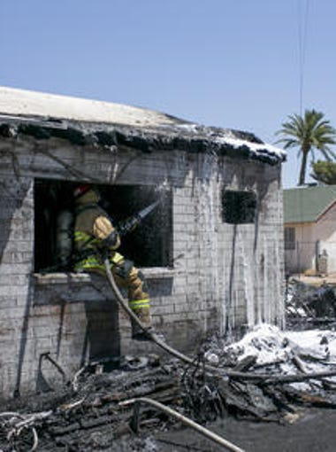 Firefighters work to extinguish a structure fire near 22nd Avenue and Madison Street on May 17, 2018, in Phoenix.