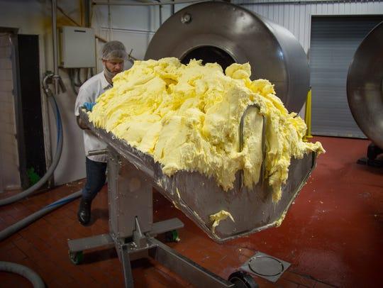 Butter maker Walker Lanham carts butter out of churn